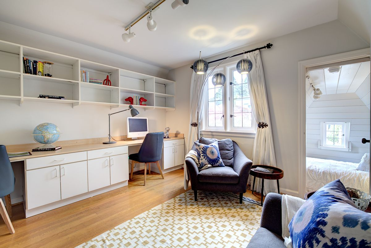 An office space has a door in the back leading to a small bed nook with vaulted ceilings