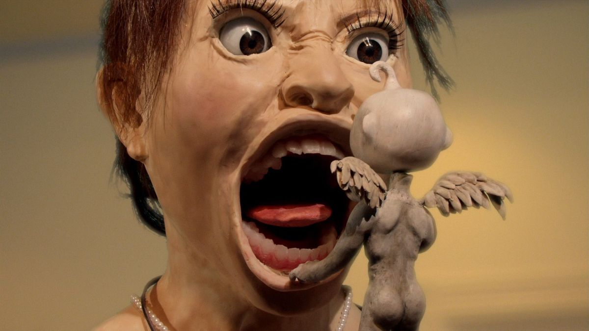 How to even describe this? Okay, it's a girl's wide-eyed Claymation head, not very realistic except for the eyes, screaming into the face of a tiny marble-colored naked winged demon-creature with its back to the camera and its ass prominently displayed. Happiness of the Katakuris is a weird movie.