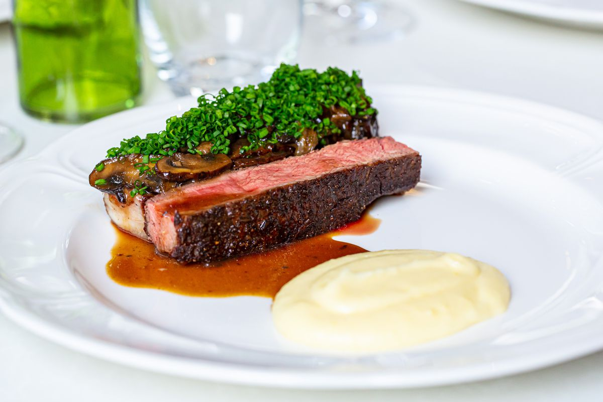 A plate of medium cooked steak topped with green herbs next to a spoonful of pomme puree