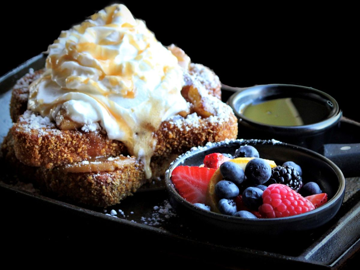 A plate of French toast with whipped cream and fruit