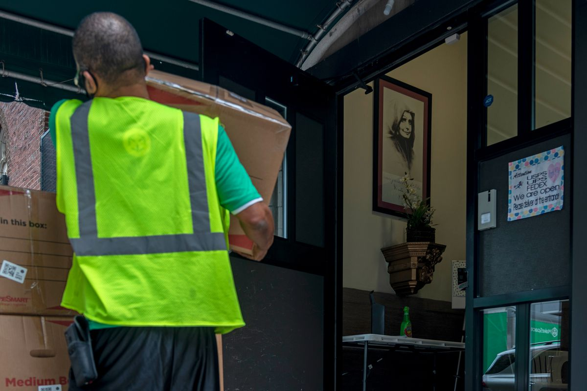 Movers carry boxes out of Centro Maria, Aug. 21, 2020.