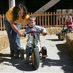 KayDe Bates of South Summit High helps Eric Swenson ride a tractor at the State Fair. Tots got to drive the toy tractors as part of an FFA exhibit.