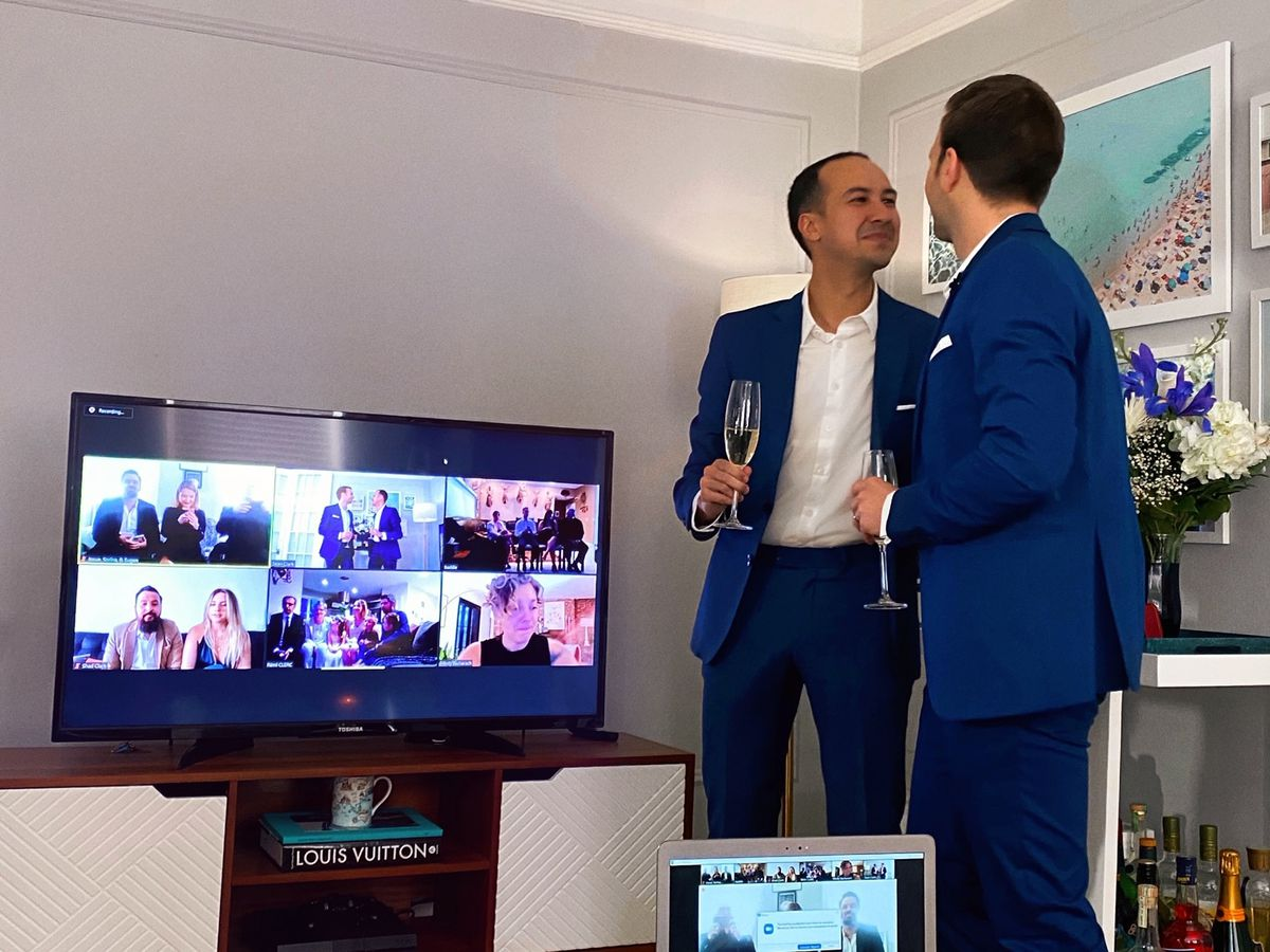 A photo of Sean and David Bouvier at their wedding, with a screen displaying a slew of friends watching via Zoom.