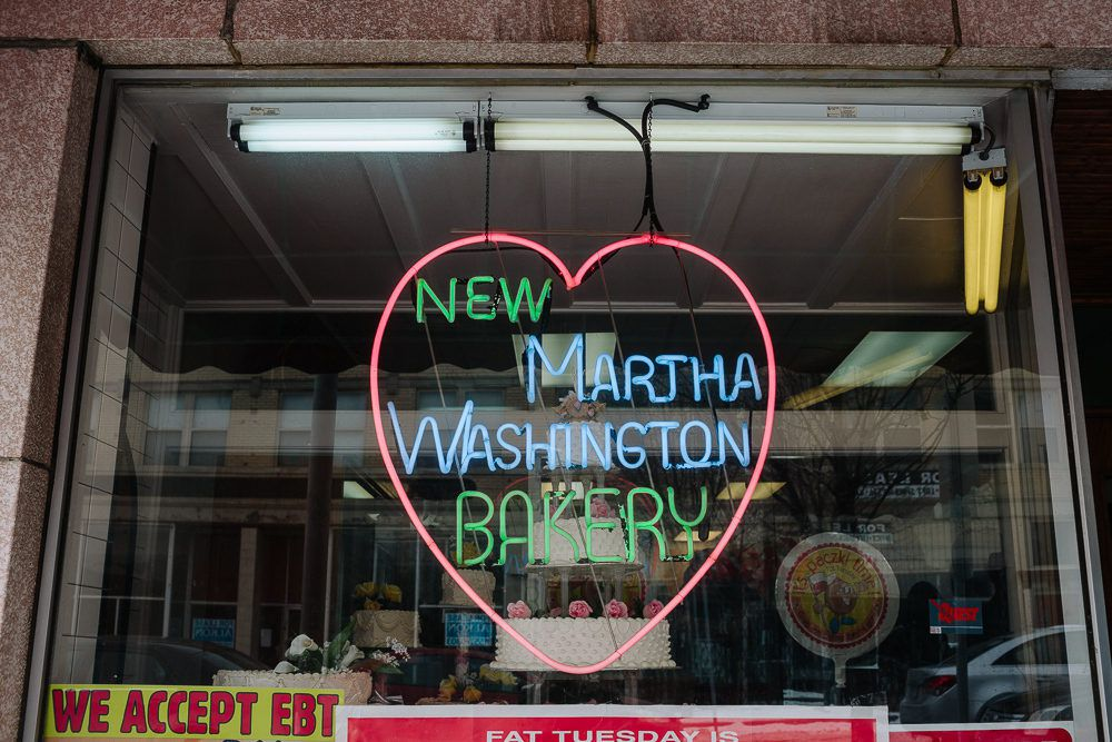 A heart-shaped neon sign hangs in the window at New Martha Washington Bakery.