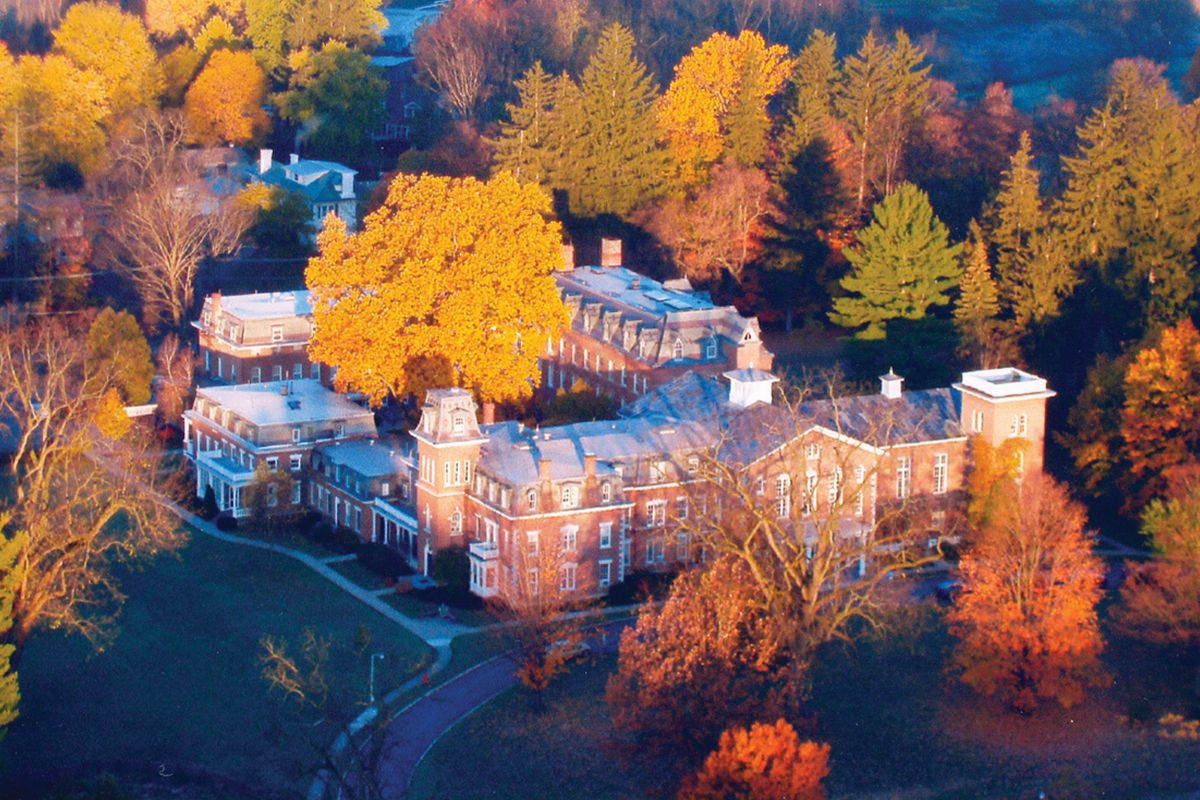 A large 19th century brick mansion with mansard roofs surrounded by autumnal foliage