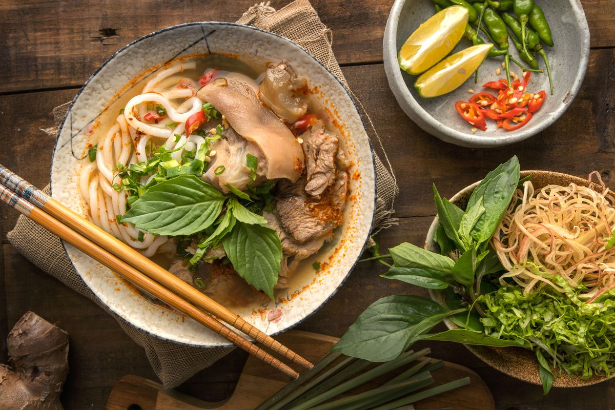A bowl of bun bo hue on a table with a side of herbs, limes, chiles, and onions