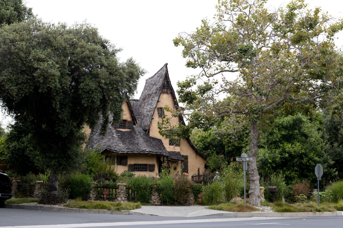 A large cottage-like home with a drooping, thatched roof is surrounded by mature trees on a corner lot on a gloomy day.