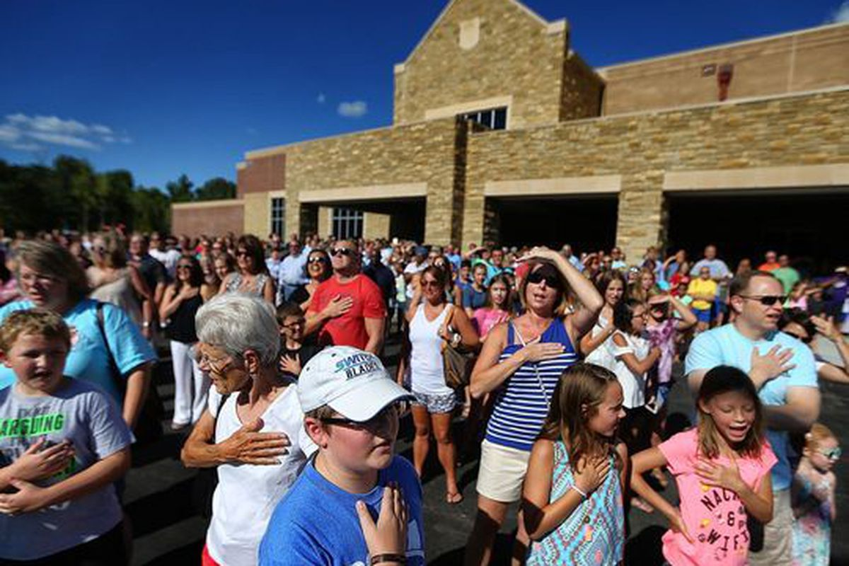 Students, teachers and parents gather for the Pledge of Allegiance outside Lakeland Middle Preparatory School during a dedication ceremony for the new school.