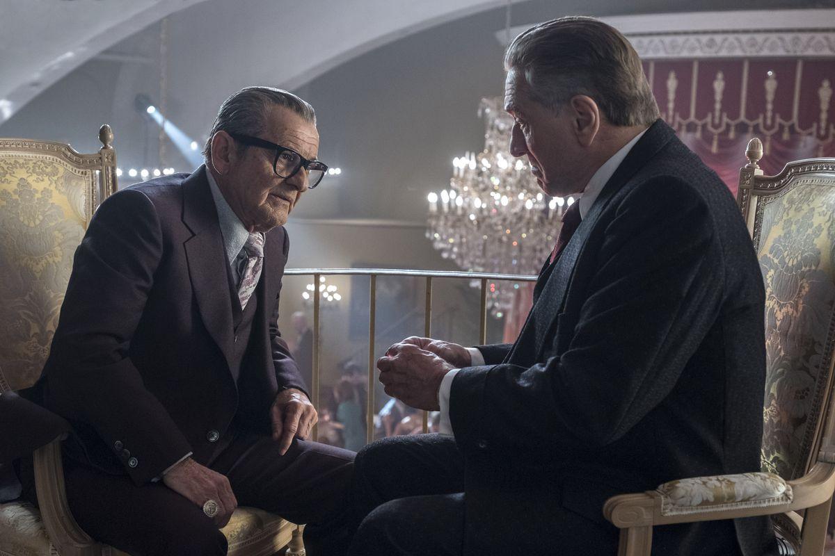 joe pesci in big glasses leans over to talk to Robert De Niro making one of those Robert De Niro faces