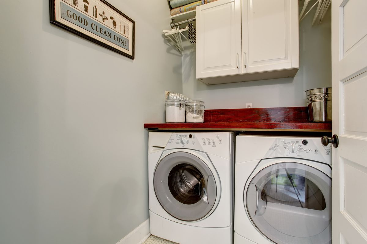 Small room with washer and dryer sitting under a countertop with a white cabinet above it.