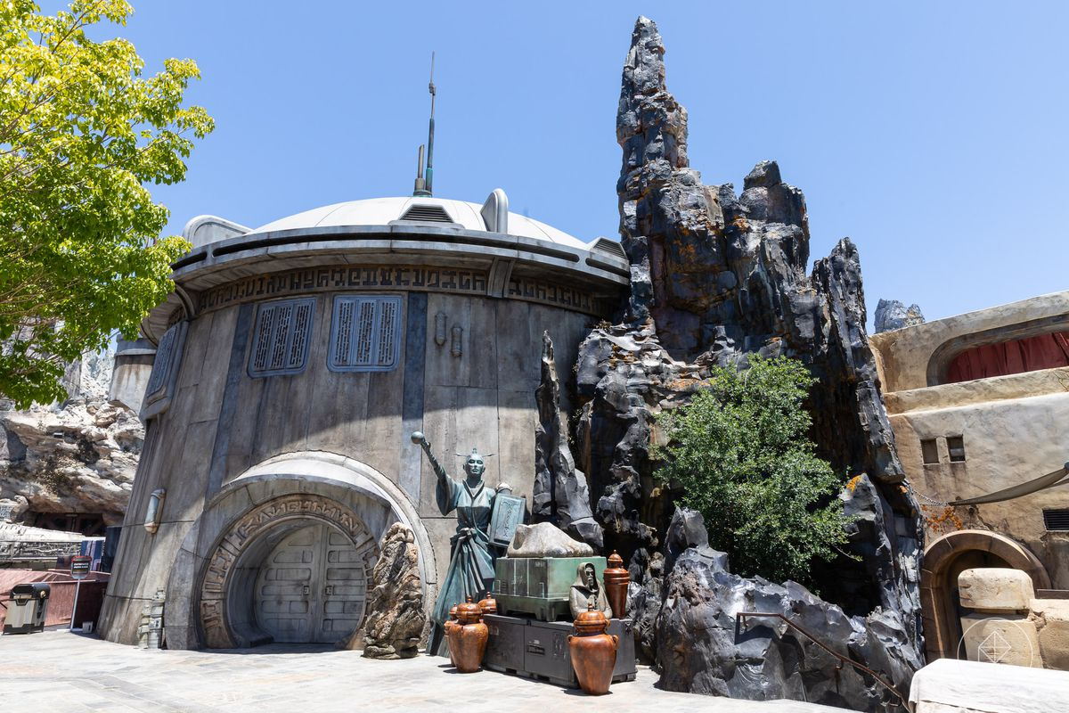 A portion of the Galaxy's Edge park in Disneyland. There is a domed building with an arched entrance. There are various sculptures of people outside of the entrance.