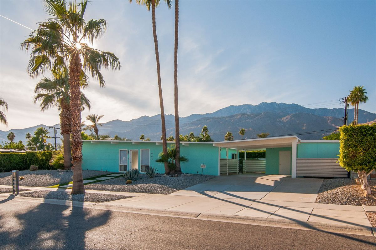 Bungalow with slightly butterflying roof and carport with backdrop of palm trees and mountains.