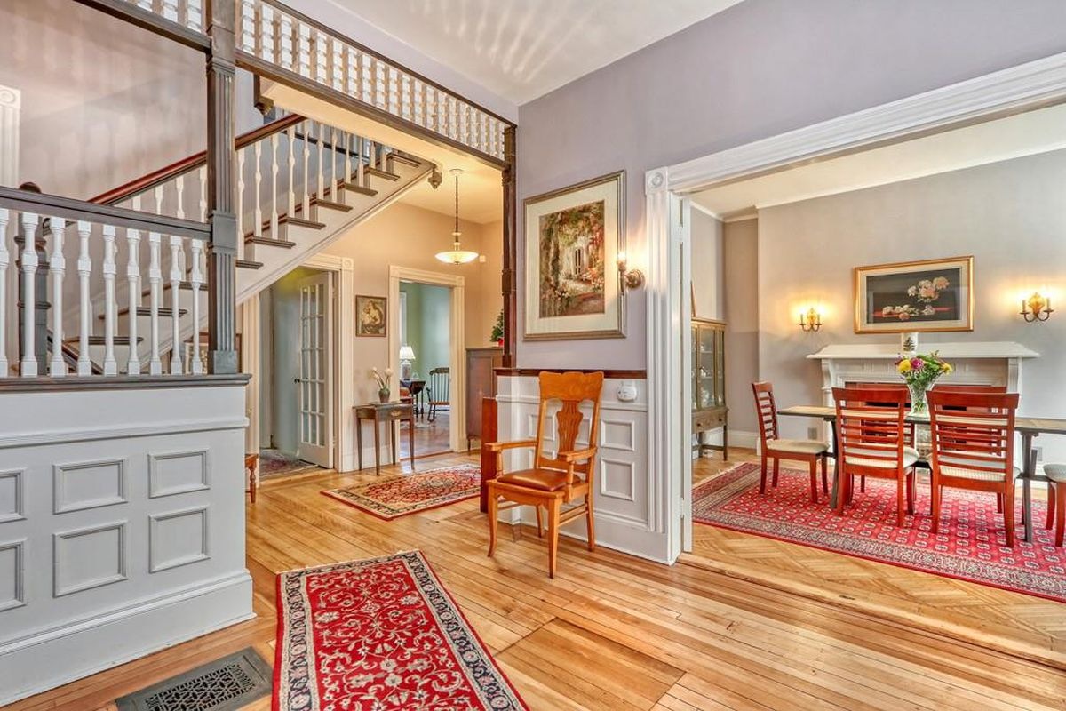 An airy entry foyer of a townhouse, with a staircase and its landing visible as well as openings to other rooms.