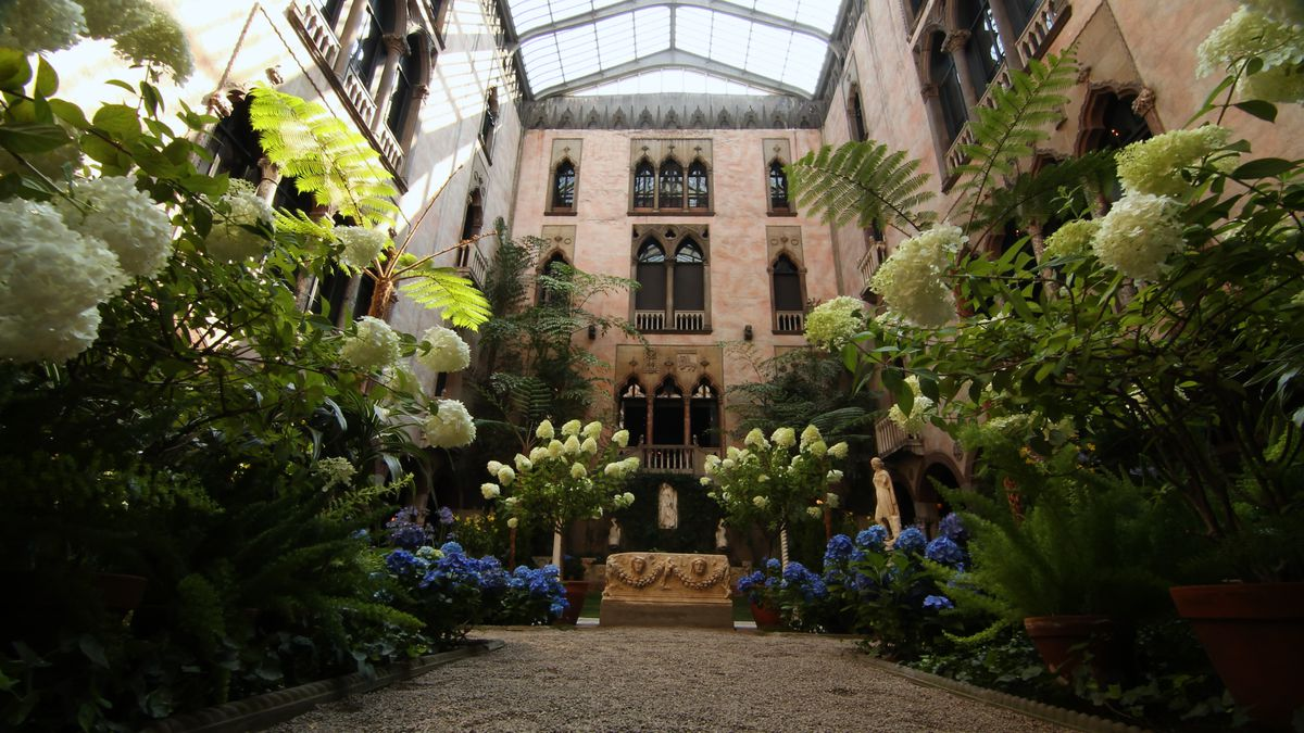 The interior of a museum with flowers, different floors and arched windows, and a ceiling made of glass that lets in light.