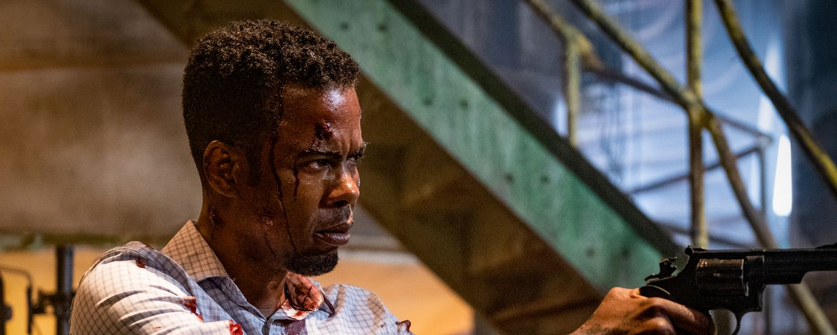 Chris Rock, crudely bandaged and spattered with blood, points a gun offscreen in Spiral: From the Book of Saw