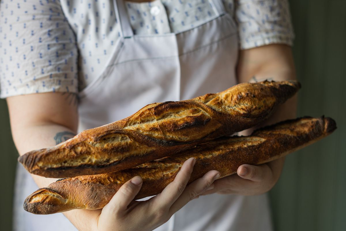 Fiona's Nicole Rucker holding baguettes up close.