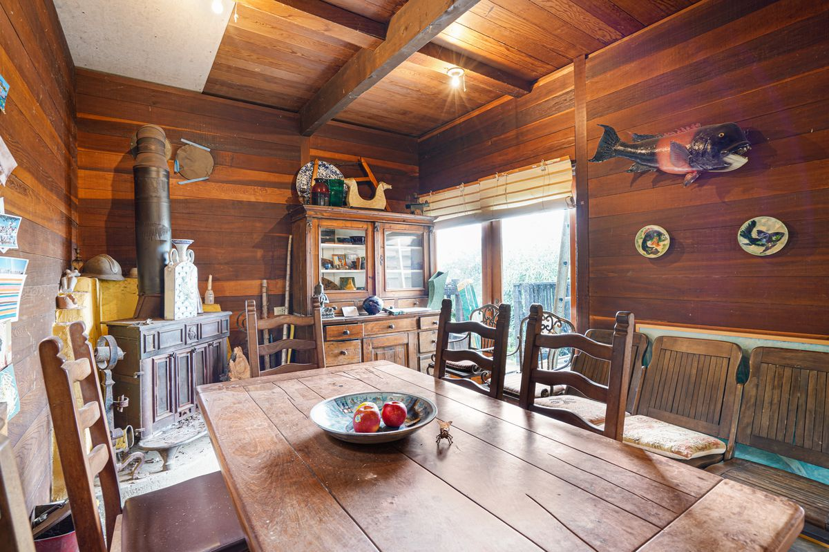 A room with wood-paneled walls and a large old stove. It's furnished with a long wooden dining room table.