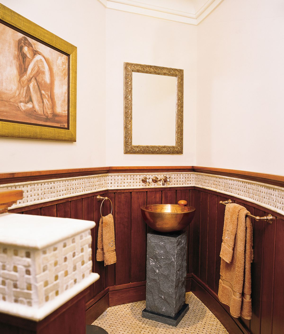 <p><strong>Rich in Detail</strong><br> A column of granite literally puts this copper vessel sink on a pedestal. At the other end of the room, the gray Kohler toilet is barely visible behind a half-wall partition. Dark wainscoting plays the mosaic tile border and floor, emphasizing the shape of the space, designed by architect Jay Haverson.</p>