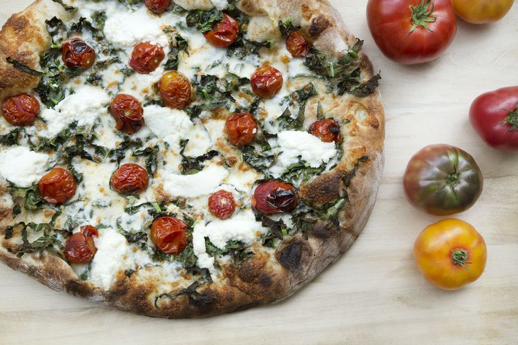 A picture of the cherry tomato pizza at Tastebud, which includes whole cherry tomatoes, ricotta, basil, and lemon