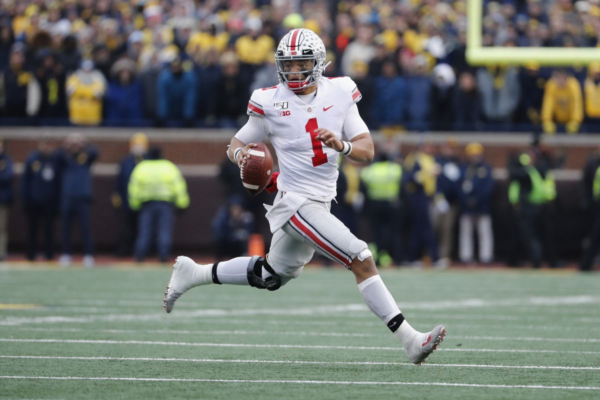 Ohio State Buckeyes quarterback Justin Fields rolls out to pass in the second half against the Michigan Wolverines at Michigan Stadium.