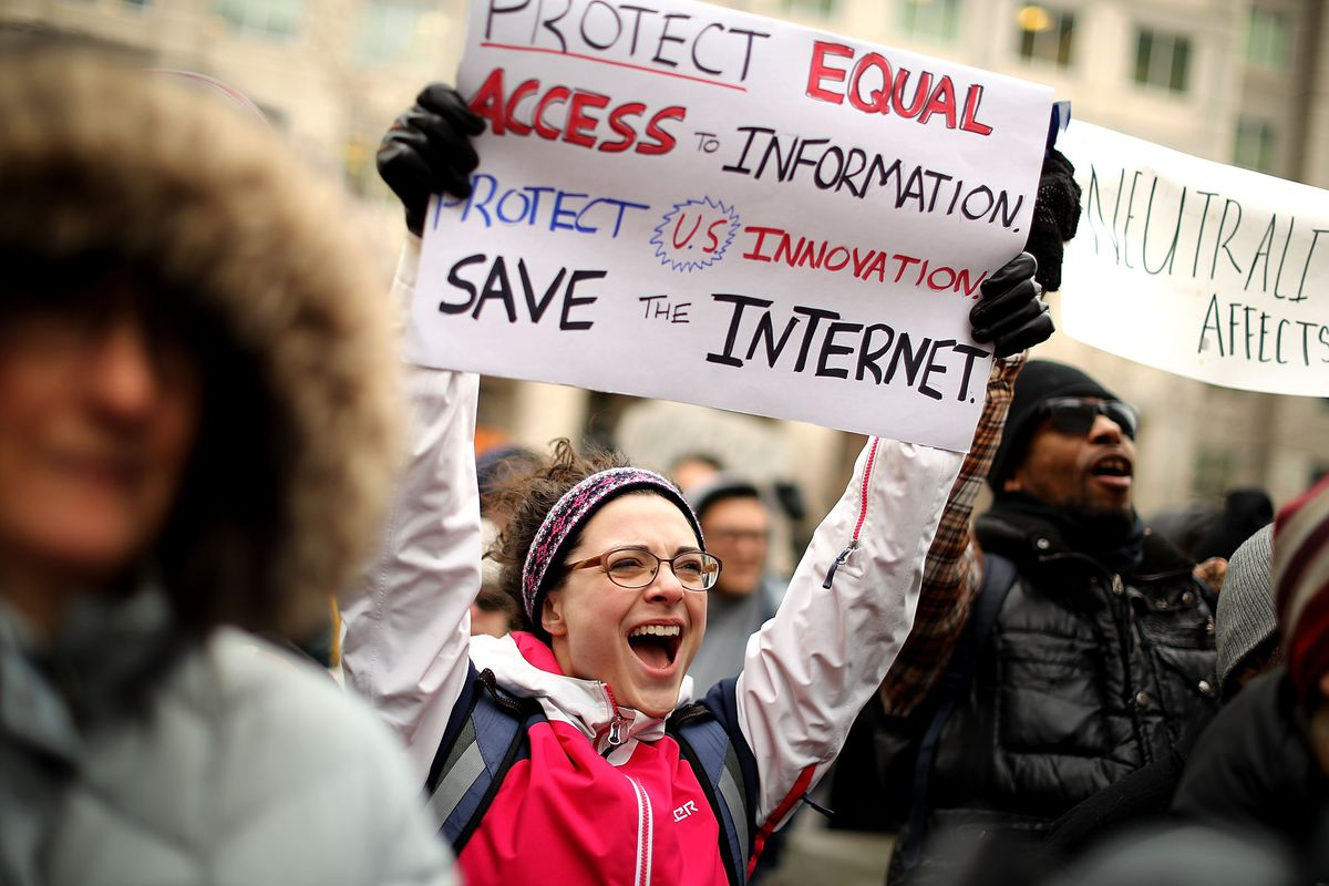 """A net neutrality protester holds up a sign that reads, """"Protect equal access = information. Protect U.S. innovation, save the internet."""""""