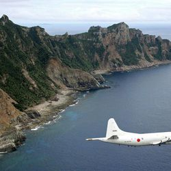 FILE - In this Thursday, Oct. 13, 2011 file photo, Japan Maritime Self-Defense Force's P-3C Orion surveillance plane flies over the disputed islands in the East China Sea, called the Senkaku in Japan and Diaoyu in China. Tokyo's outspoken governor says the city has decided to buy a group of disputed islands to bolster Japanese claims to the territory, a move that could elevate tensions with China.