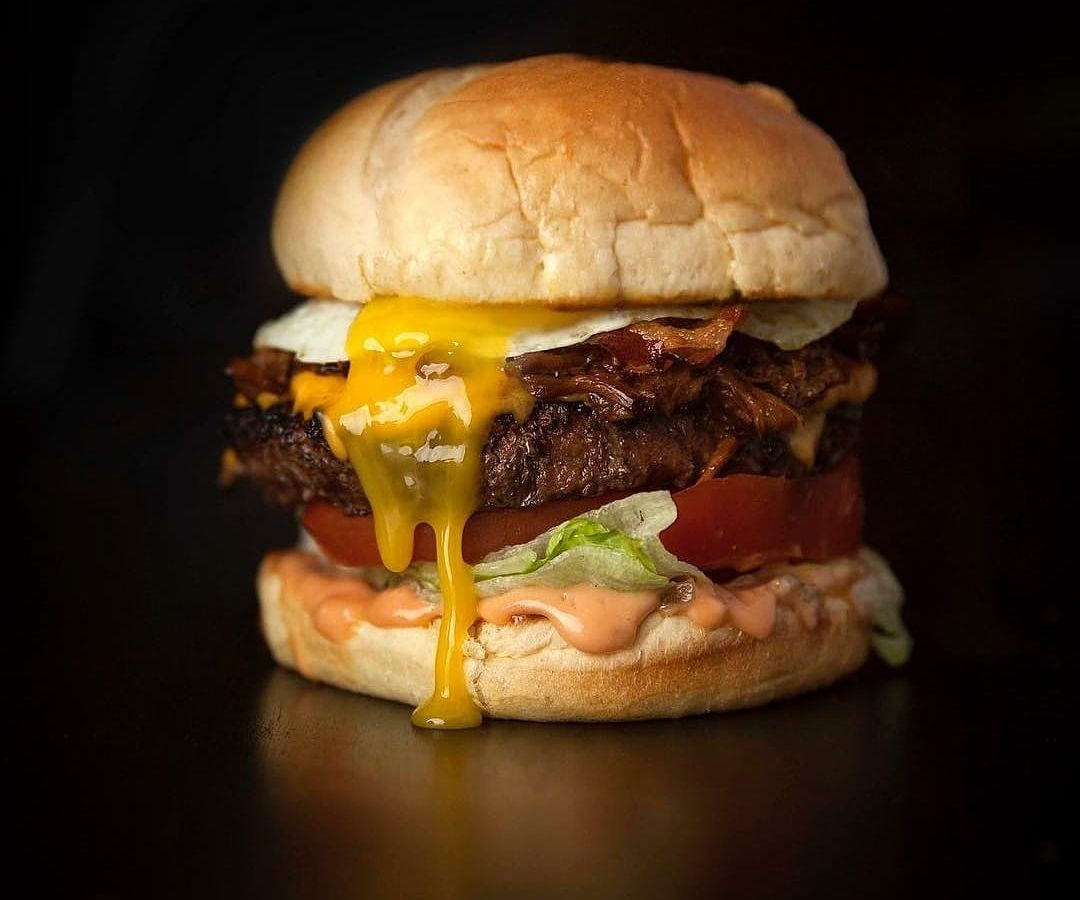A burger with cheese and an egg on top