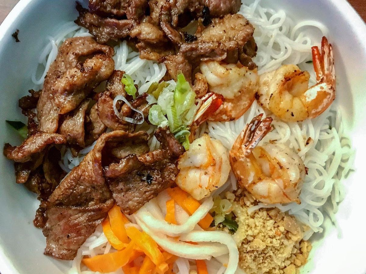A bowl of rice noodles with pork, shrimp, veggies, and crushed peanuts.