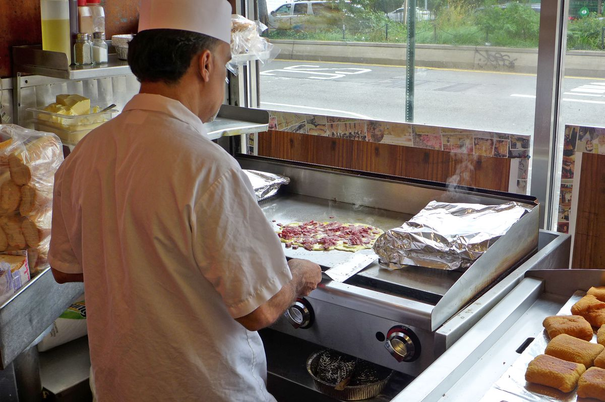 With his back to us, a cook makes on omelet on a flat top griddle...