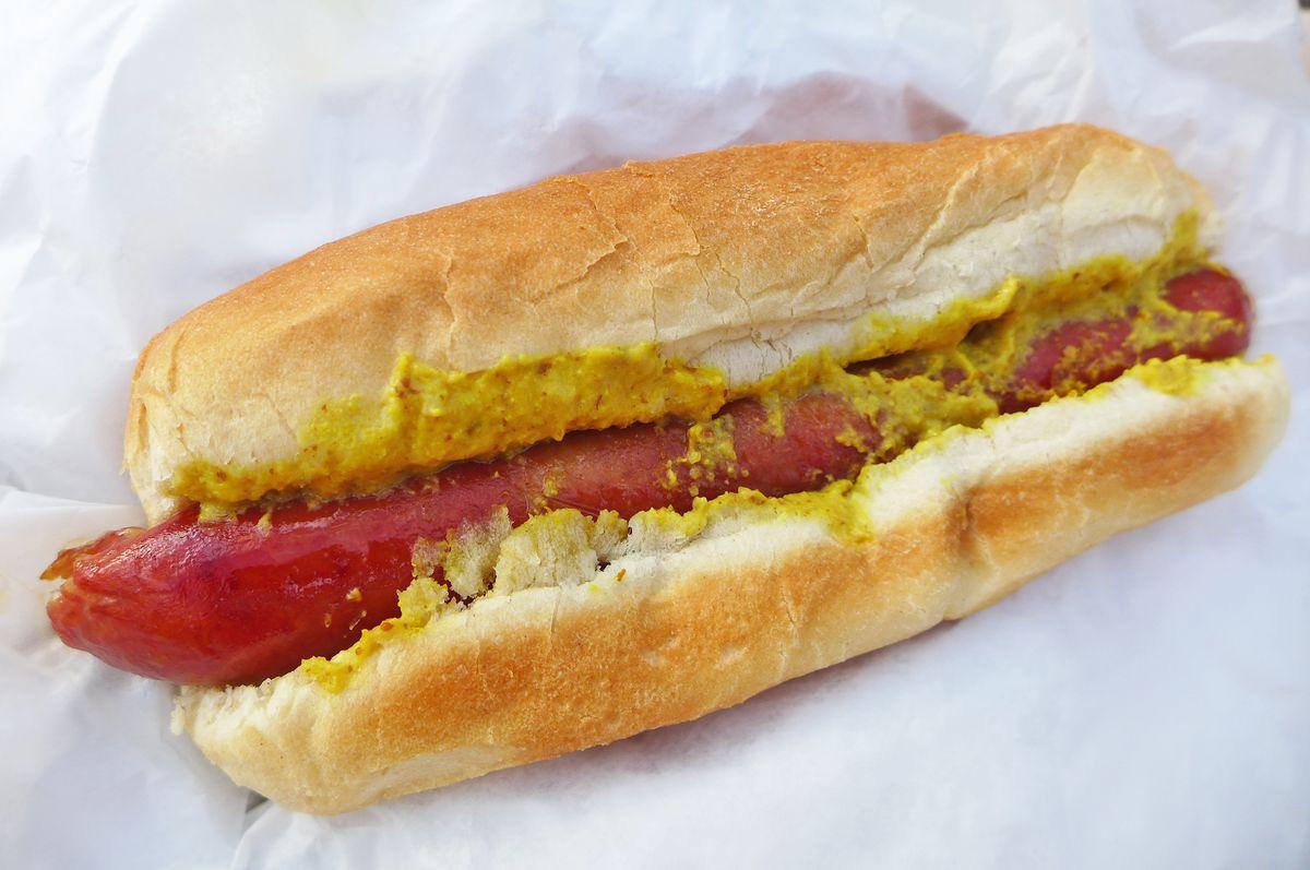Hot dog on a long bun slathered with yellow mustard.