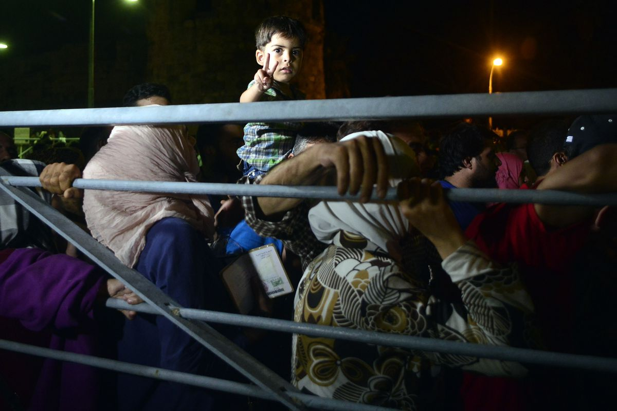 Syrian refugee families wait in line in a crowded makeshift registration center on the Greek Island of Kos.
