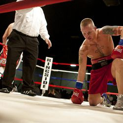 """Allen Litzau kneels after taking a series of blows during the WBU boxing match between Litzau and hometown favorite Chris """"KidKayo"""" Hernandez at the South Towne Expo Center. Fernandez won the bout after four rounds, Saturday, Dec. 15, 2012."""