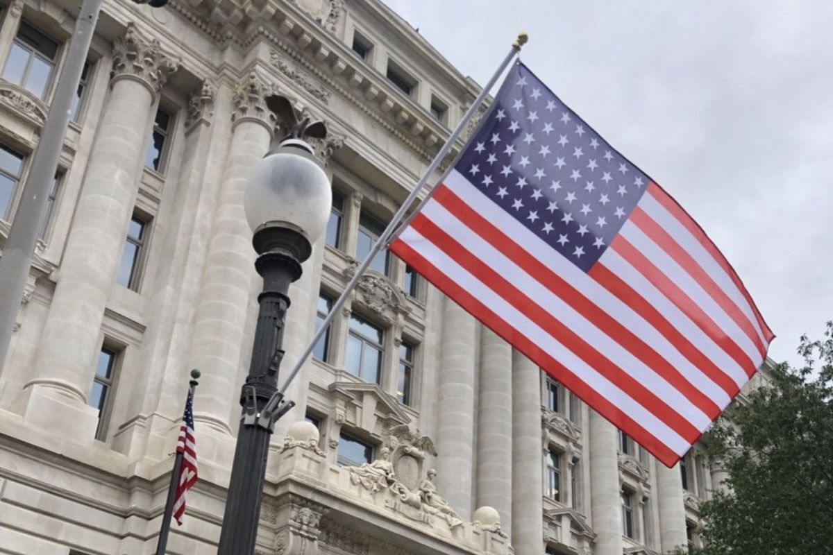 A red, white, and blue striped flag with 51 white stars hangs on a light pole outside a stately government building.