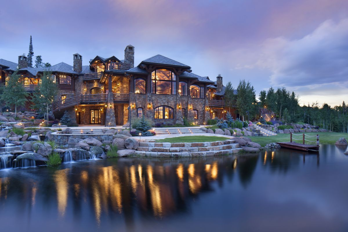 Massive rustic mountain lodge with stone and log facade with man-made lake in the front with small waterfalls.