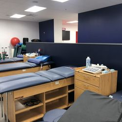 The training room includes multiple upright seats for rehab, with the NJIT logo on each seat.