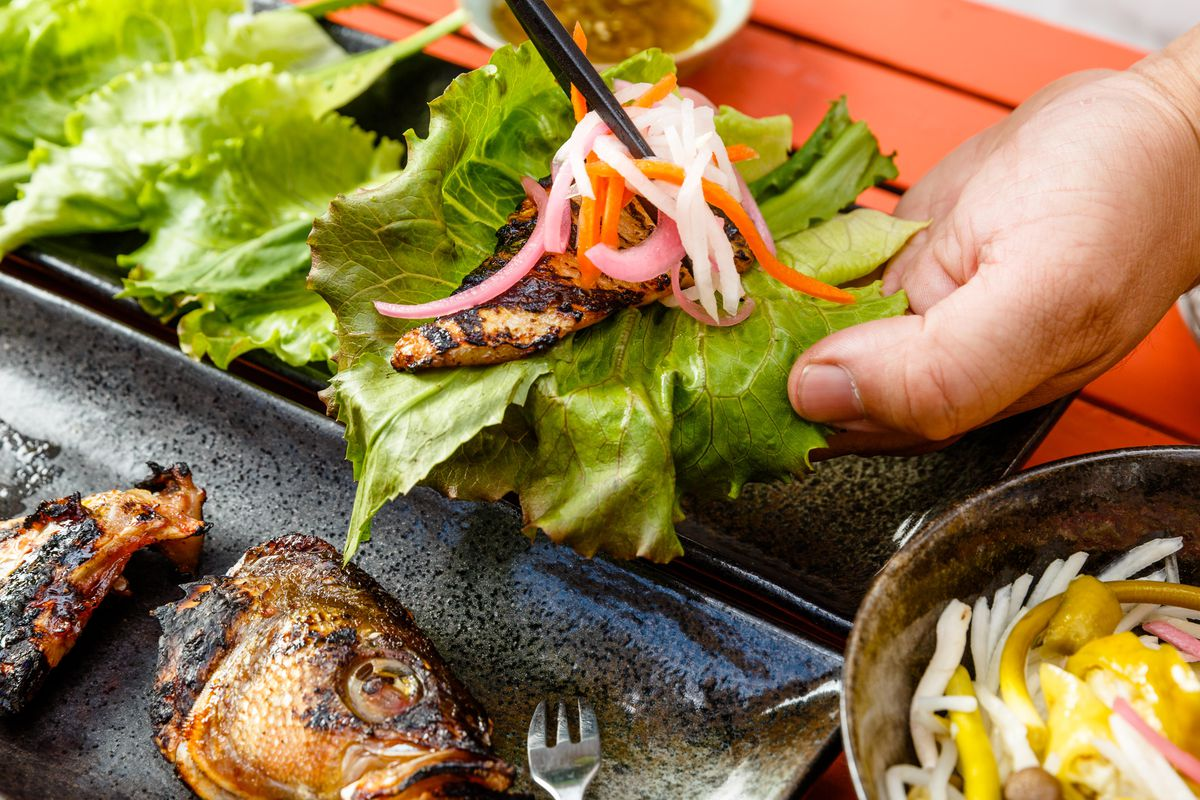 A patron adds slaw to a fish belly lettuce wrap