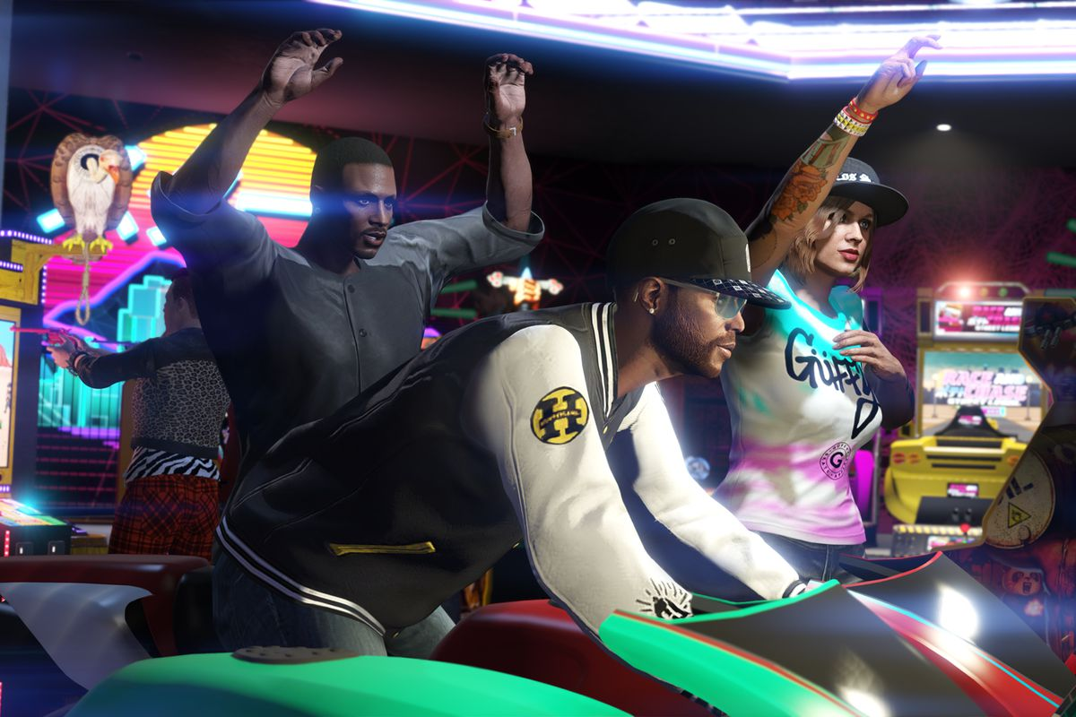 a black man playing an arcade racing game while two friends look on in Grand Theft Auto Online's Diamond Casino Heist update