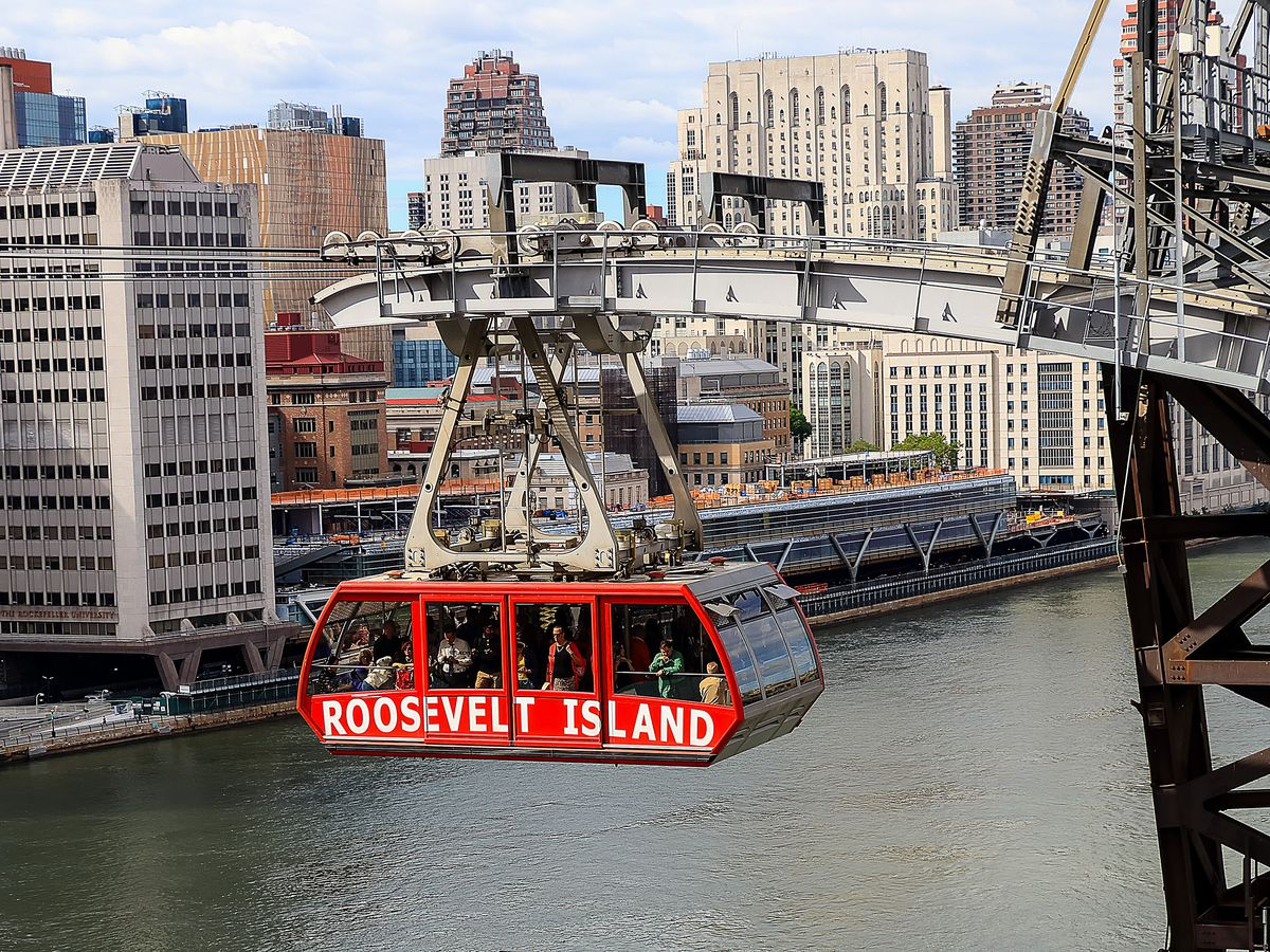 A red tram is suspended over a body of water. The words Roosevelt Island are written on the side of the tram car. In the distance are large city buildings.
