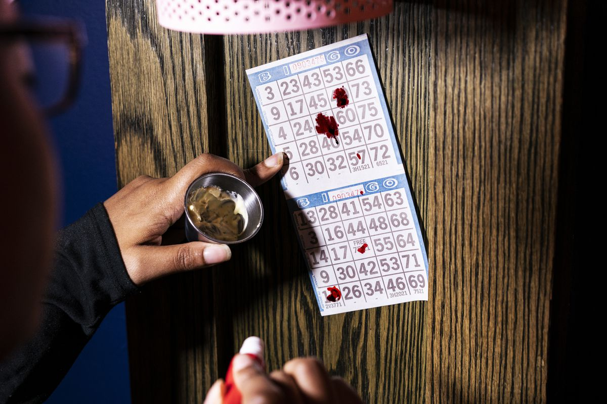 An overhead shot of a Bingo card and a hand holding a dauber and a metal cup with a shot of liquid in it