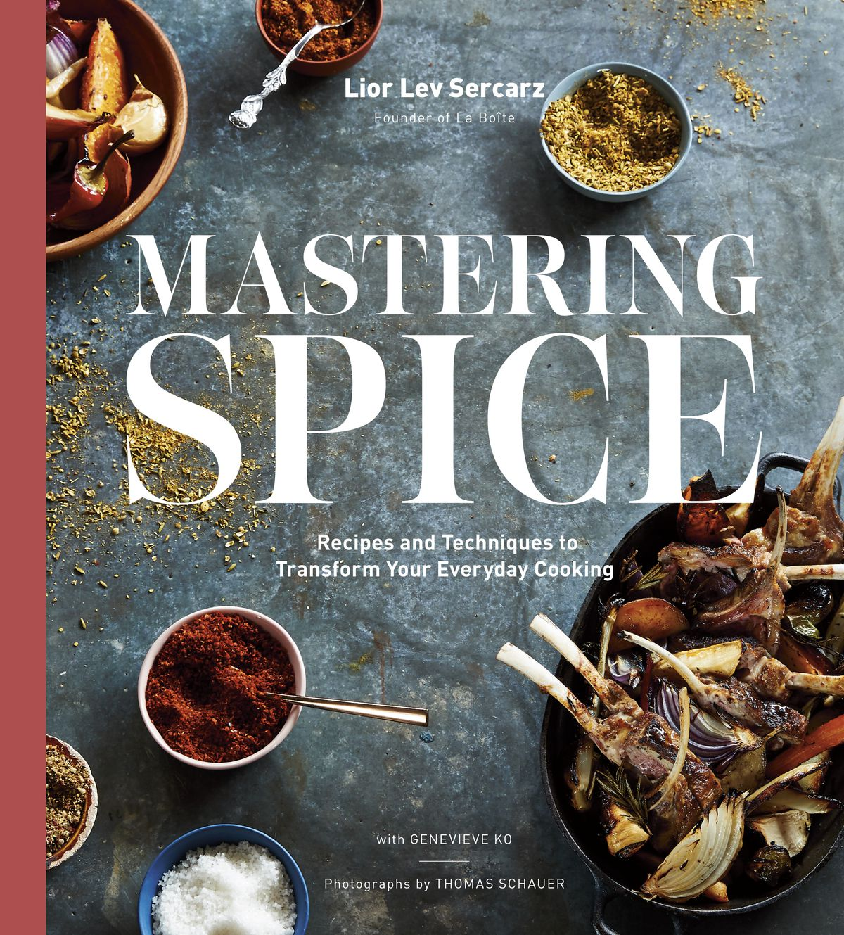 """Cover of """"Mastering Spice"""" cookbook, showing spiced powders and dried vegetables scattered on a dusty blue table"""
