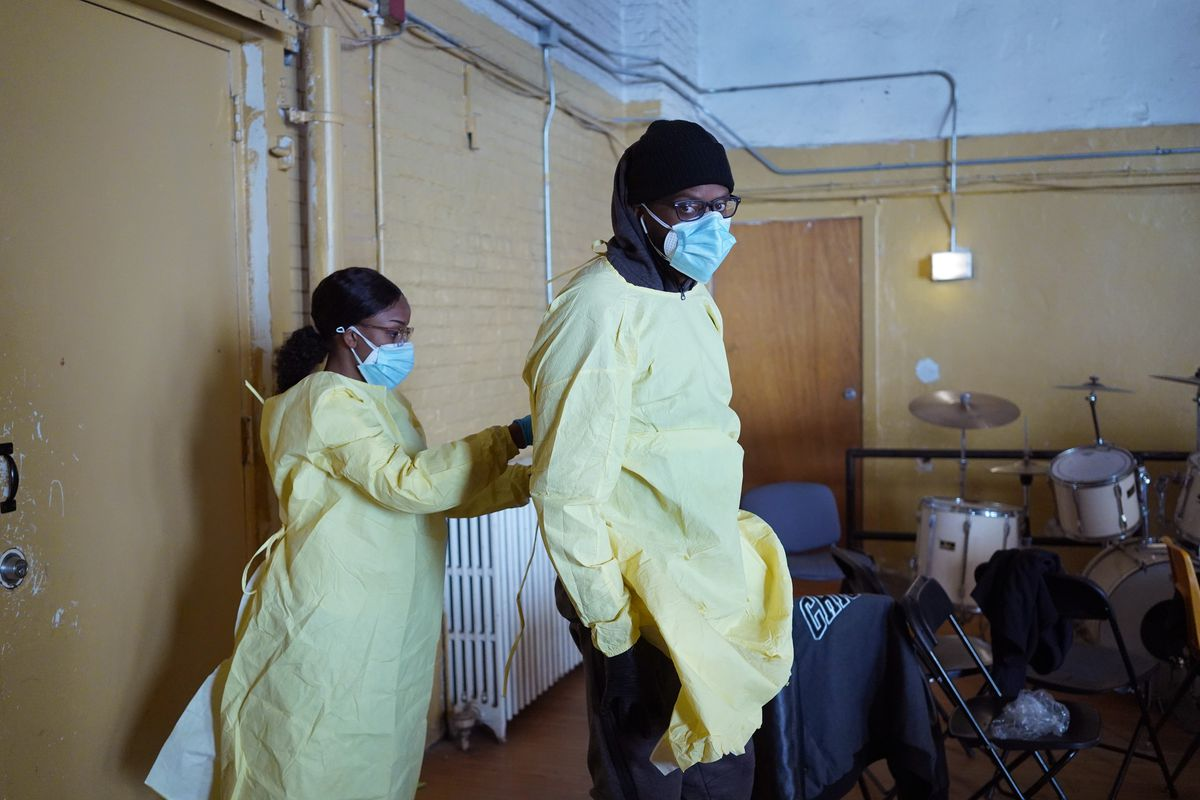 Workers suit up in personal protective equipment as they prepare to open a COVID-19 test site in the Englewood neighborhood on Thursday.