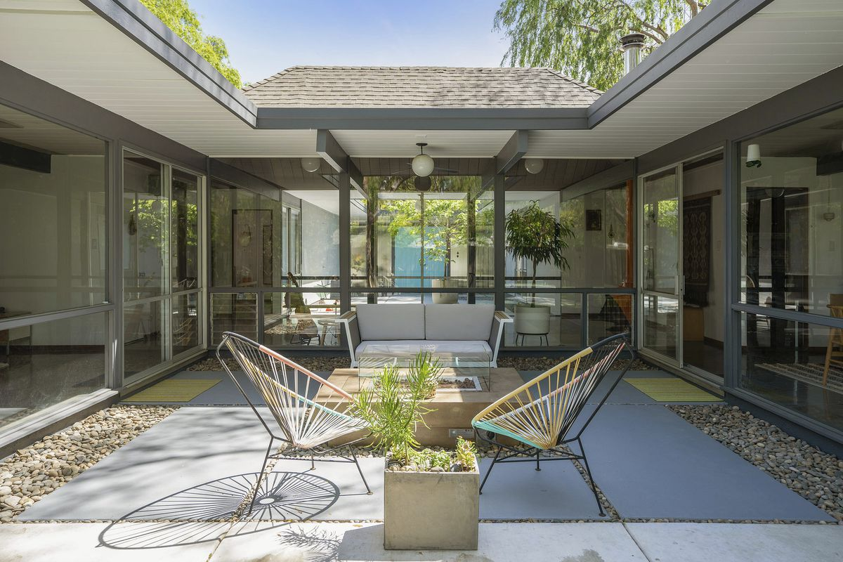 A sunny courtyard flanked on all sides by floor to ceiling windows that look inside the home.A big cut out in the courtyard reveals a shingled roof.
