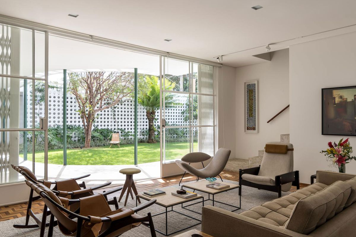 Interior shot of white-walled living room looking out onto a grassy courtyard via a wall of sliding glass windows. The space is furnished with midcentury pieces in neutral colors.