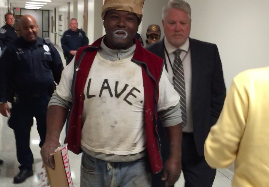 """Larry Vaughn is escorted out of an Indianapolis Pubic School Board meeting on Oct. 27, 2015, after he called the board members """"child molesters."""" Vaughn is a candidate for IPS school board."""