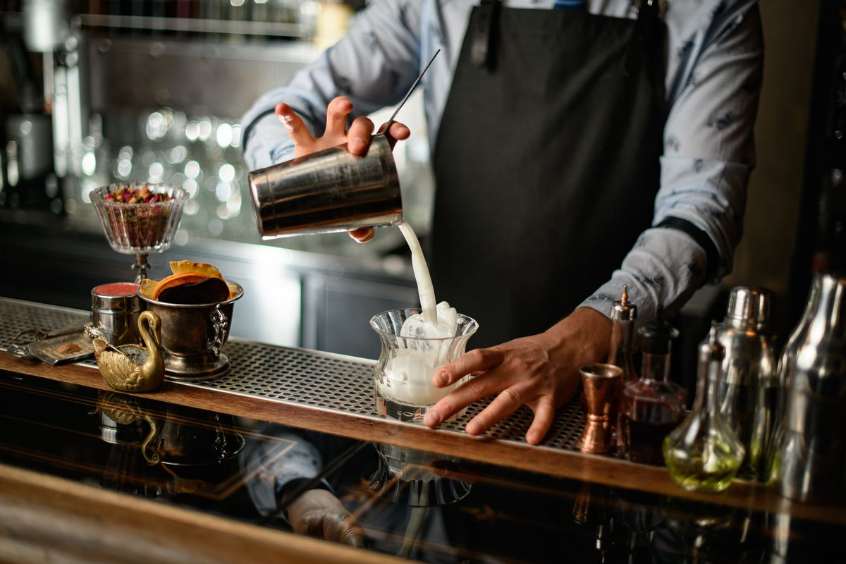 A bartender with a black apron mixes a drink into a glass