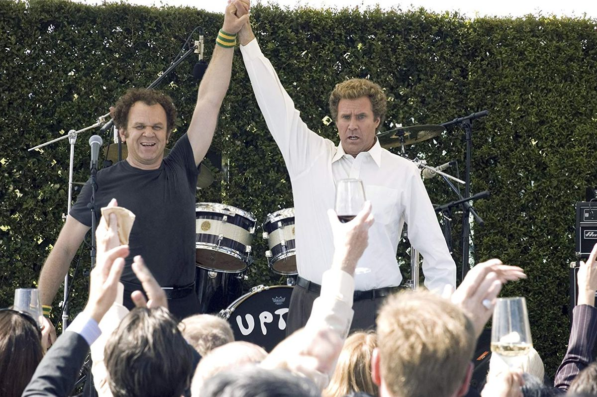 Reilly and Ferrell high-fiving in front of a drum kit