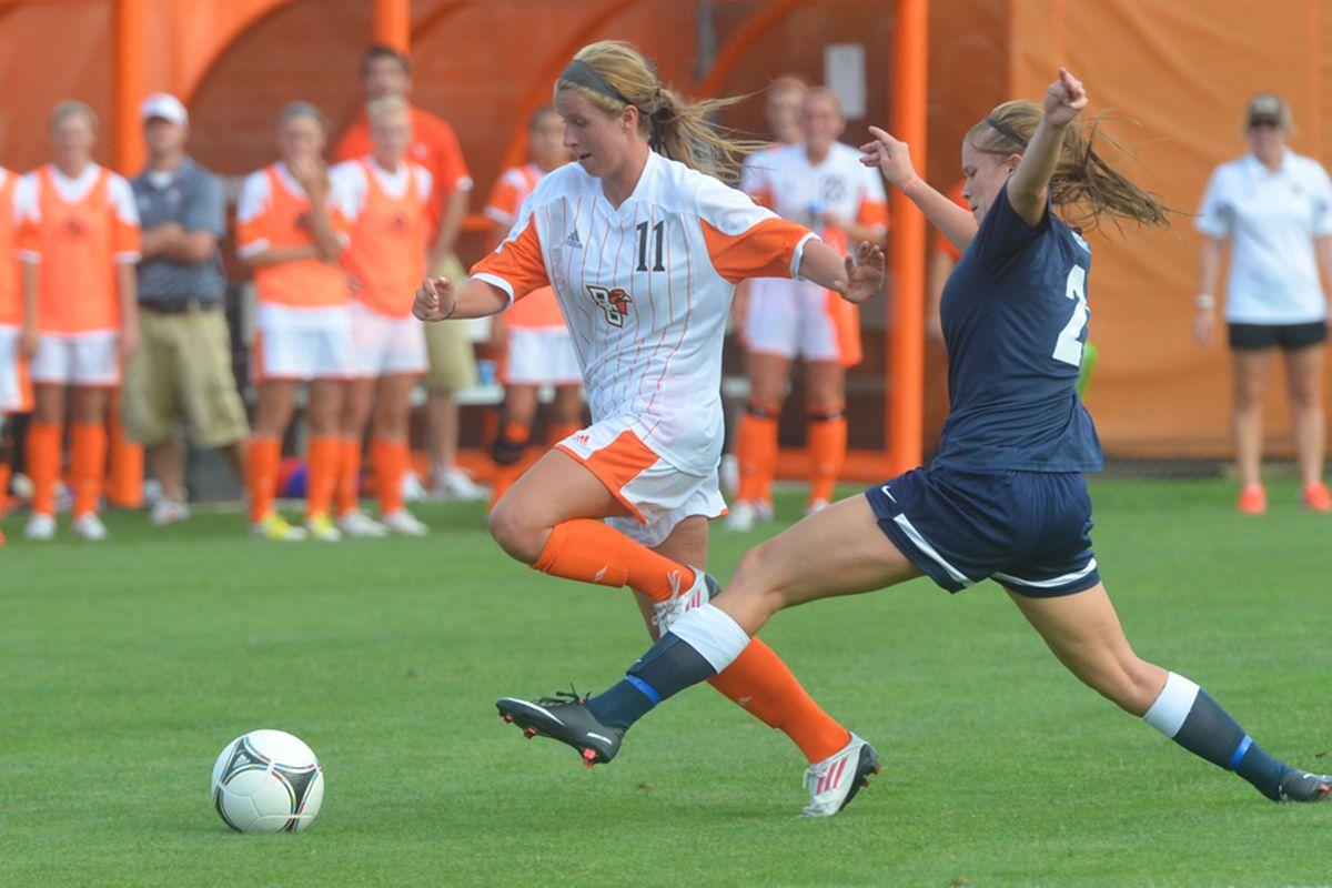 Wideman dribbles through a defender while her teammates watch on.
