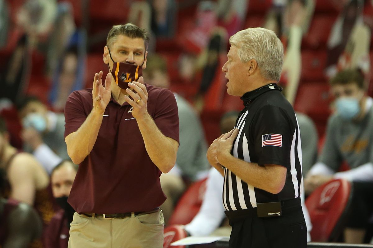 Loyola Ramblers head coach Porter Moser discusses a call with an NCAA referee during the second half at the Kohl Center.