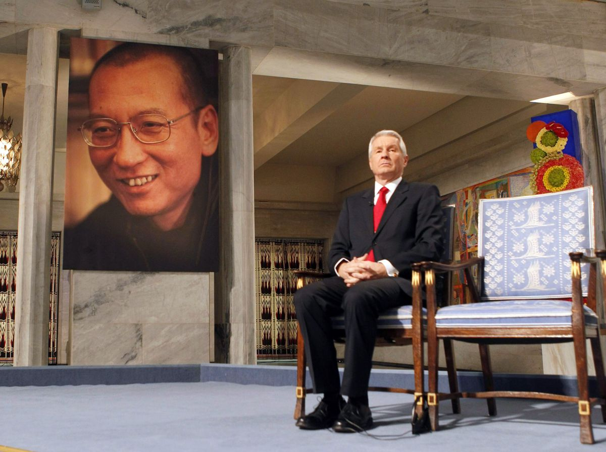 A man sits next to an empty chair with a photo of Liu Xiaobo in the background