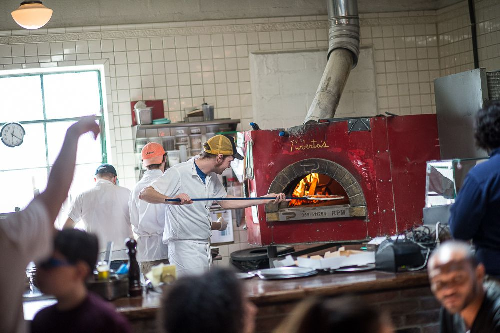 A man inserts a pizza into a red wood-fired oven.